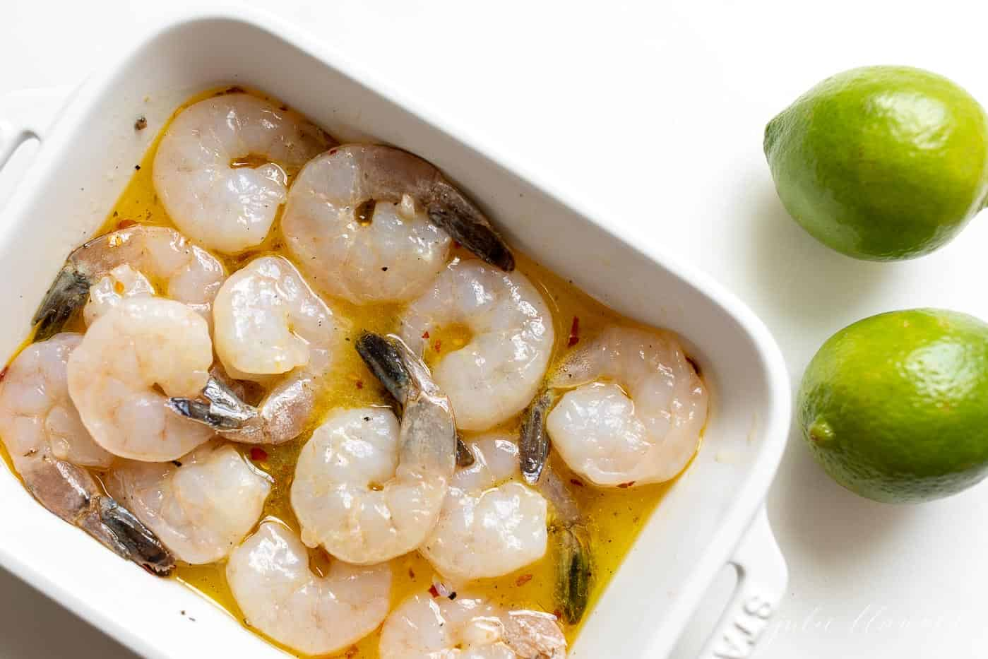 A white dish with marinating tequila lime shrimp for grilled shrimp skewers.