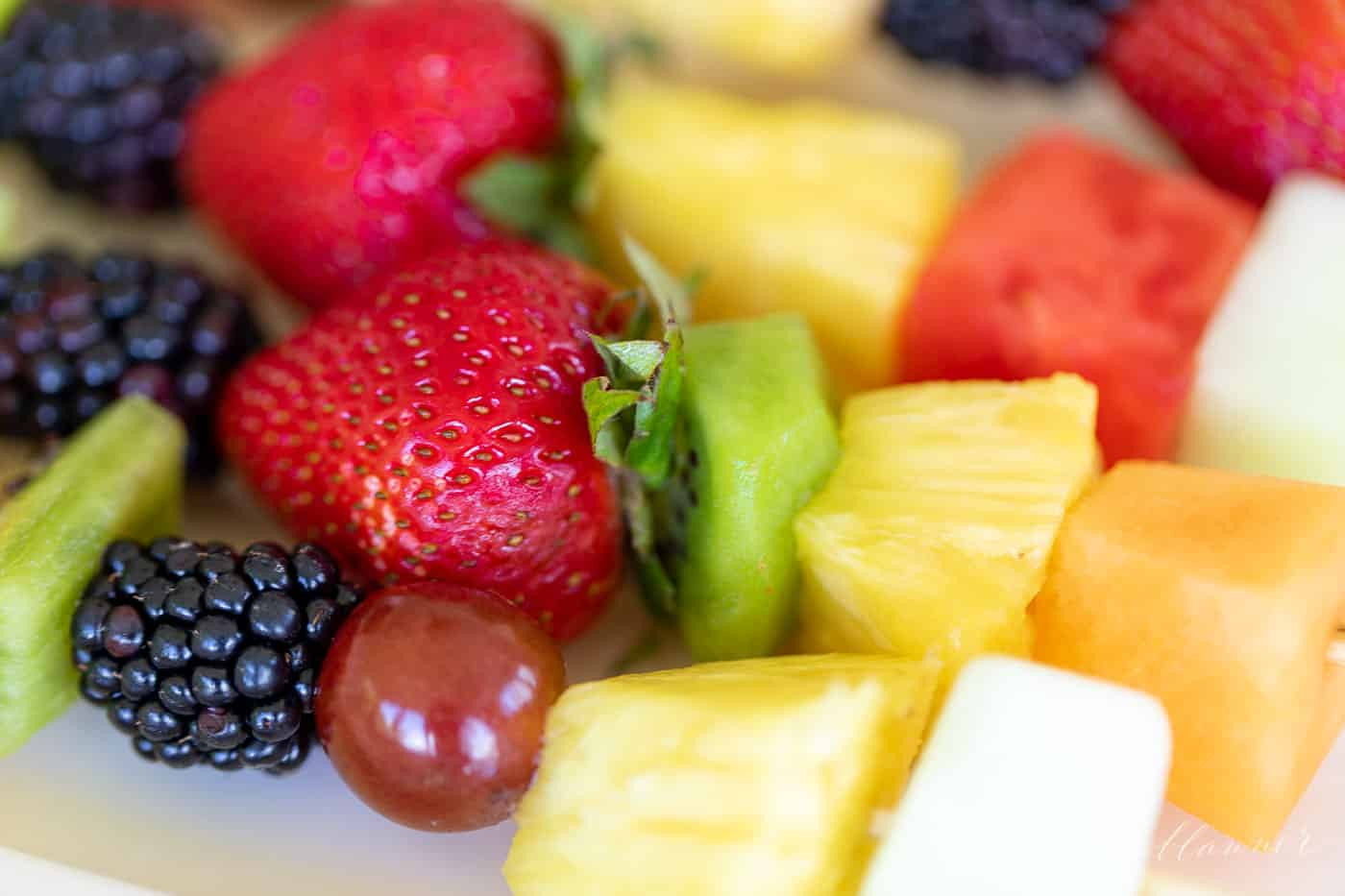 Close up of colorful fruit kebobs.