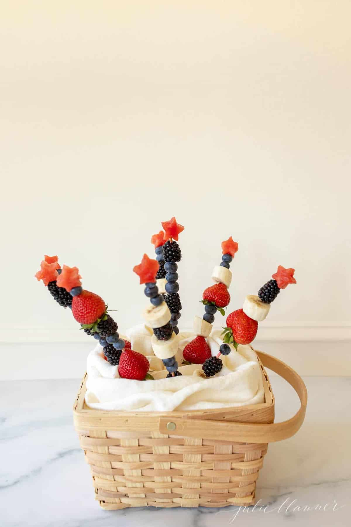 A marble surface with fruit skewers sticking out of the inside.
