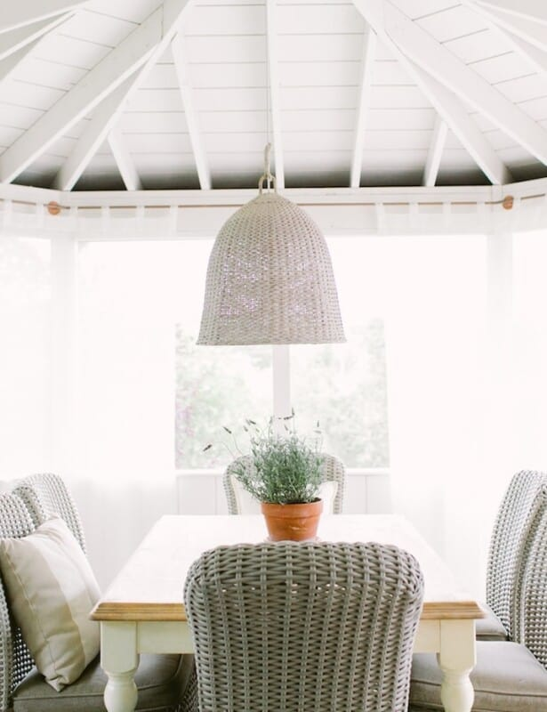 Wicker seating at a dining table on a screened in porch, a pot of English lavender as the centerpiece.