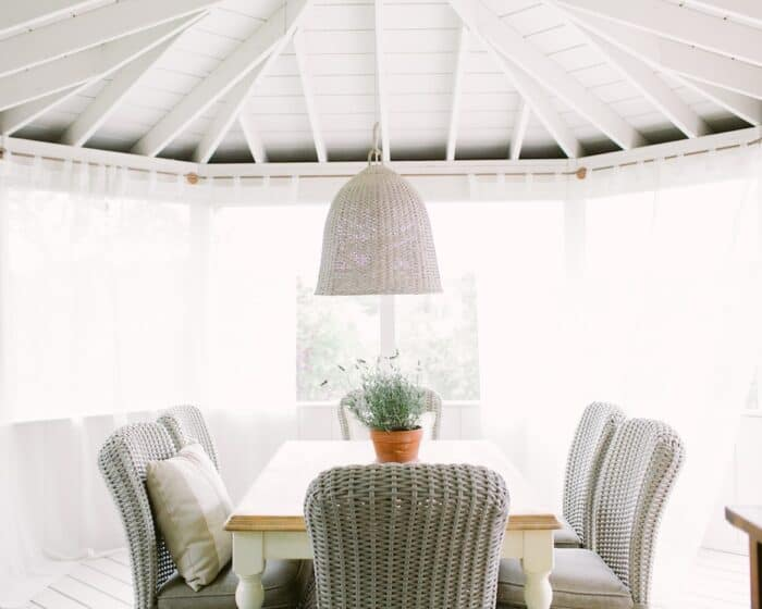 Wicker seating at a dining table on a screened in porch.