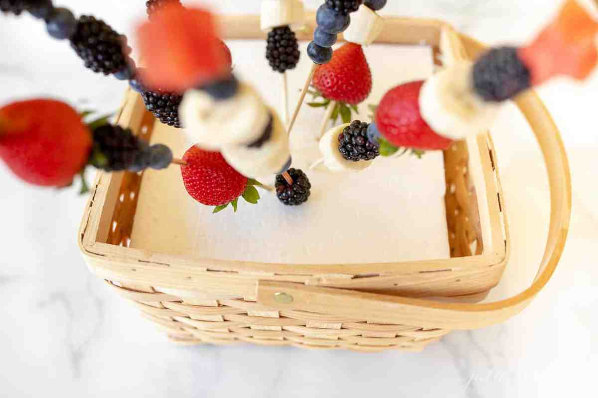 A marble surface with a wooden basket, sheet of white foam inside, fruit skewers shooting out.