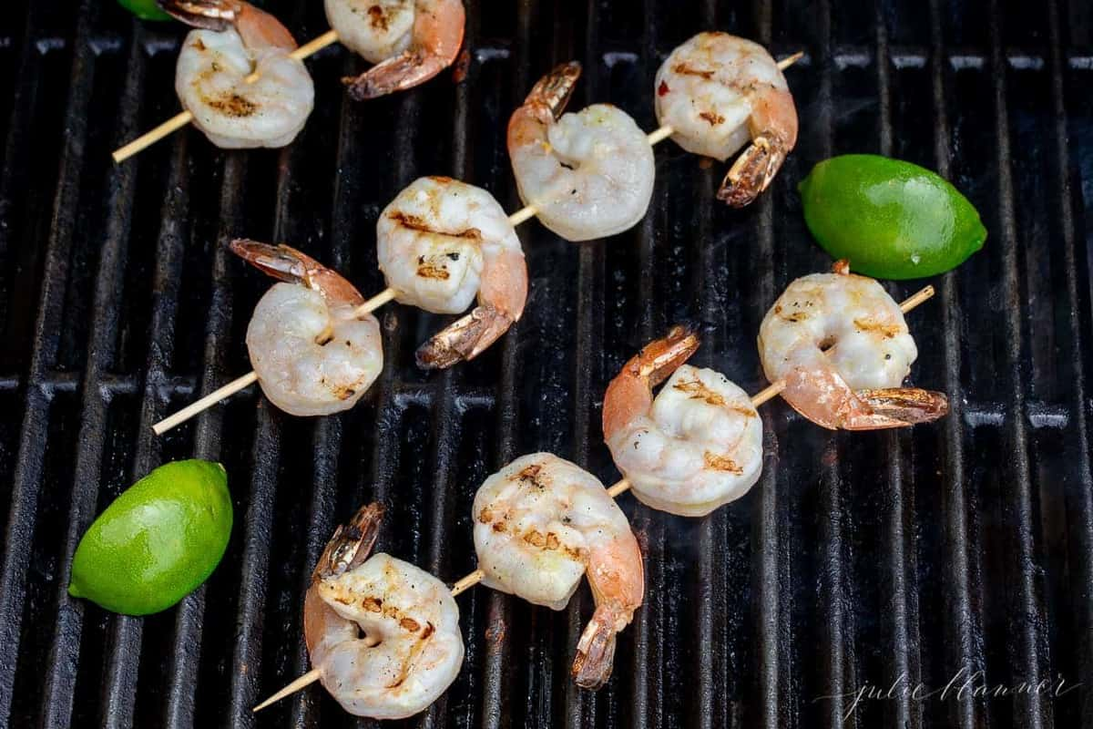 Shrimp skewers on the grill with sliced limes on the side.