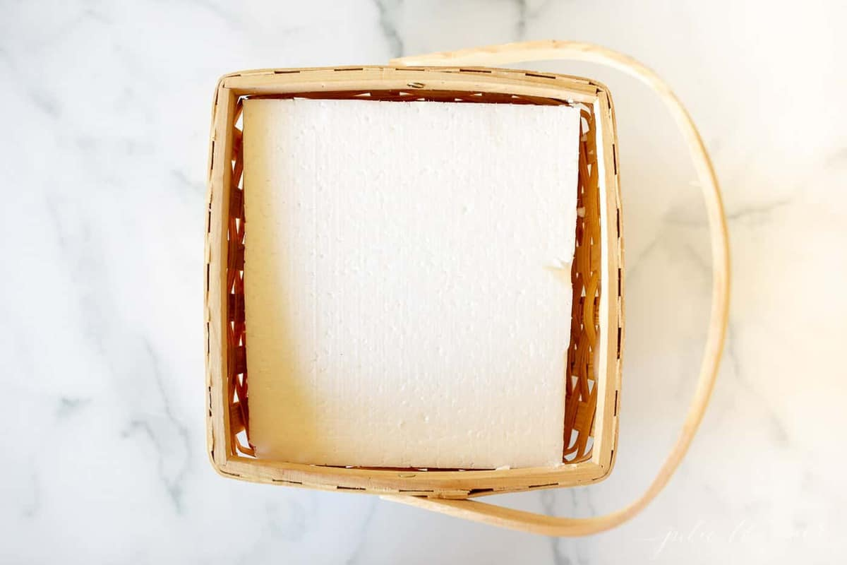 A marble surface with a wooden basket, sheet of white foam inside.