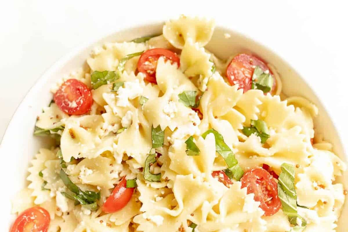 Uma tigela branca cheia de uma receita de salada de macarrão frio.
