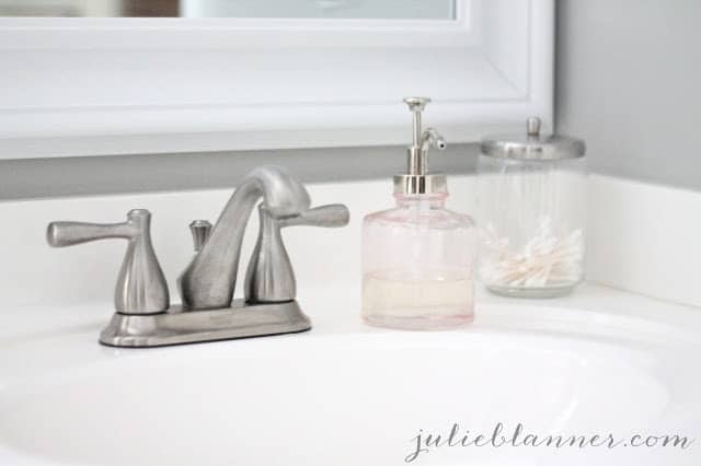 bathroom sink with a silver faucet and gray knitting needles paint color on the walls.
