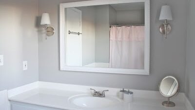 Bathroom with a white cabinet, large white framed mirror and gray walls.