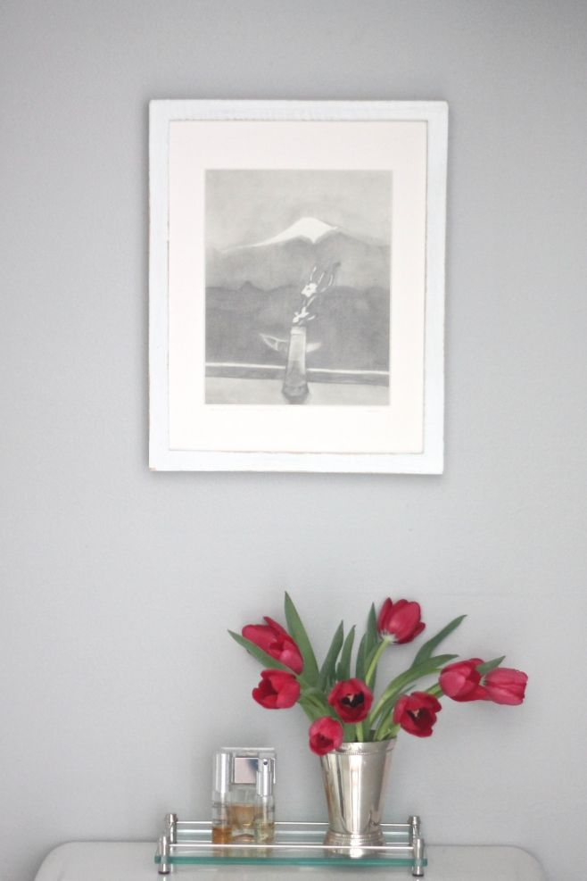 Decor over a toilet, including Knitting Needles wall paint, a vase of red tulips and framed art.