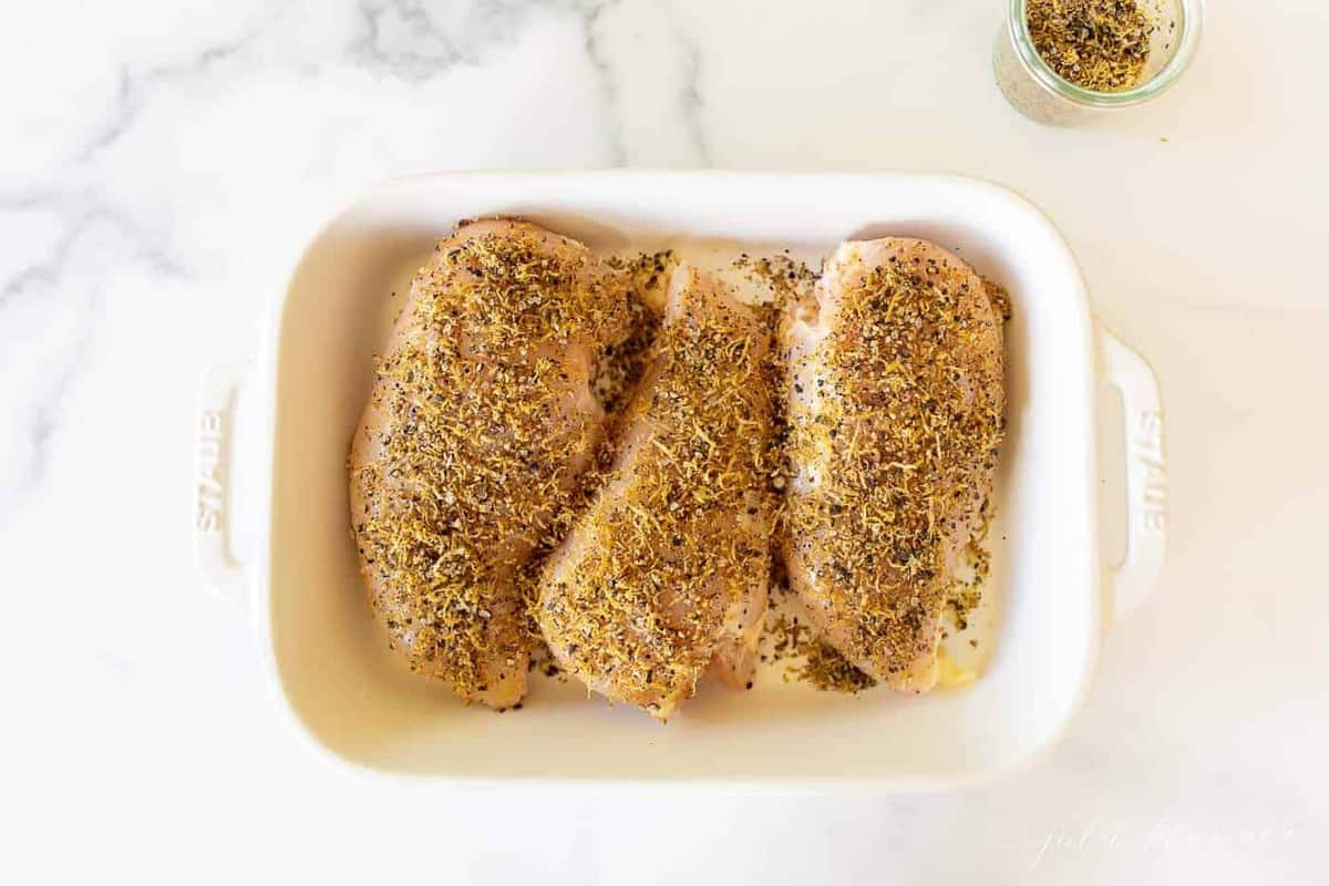 Three raw chicken breasts covered in lemon pepper seasoning in a white baking dish, white basting brush on the top.