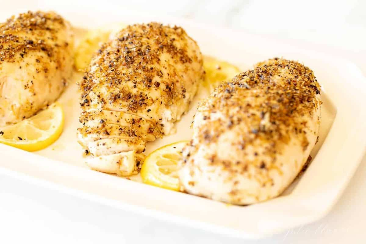 A white tray with a recipe for lemon pepper chicken and slices of lemon.