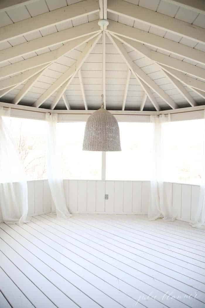 A white painted screened in porch with a basket lantern before furniture is added.