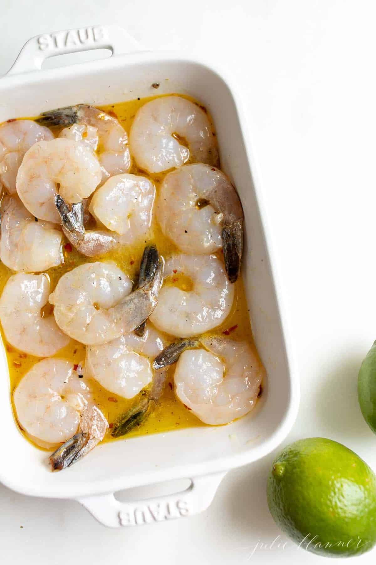 Pineapple shrimp marinade with large shrimp in a white dish.