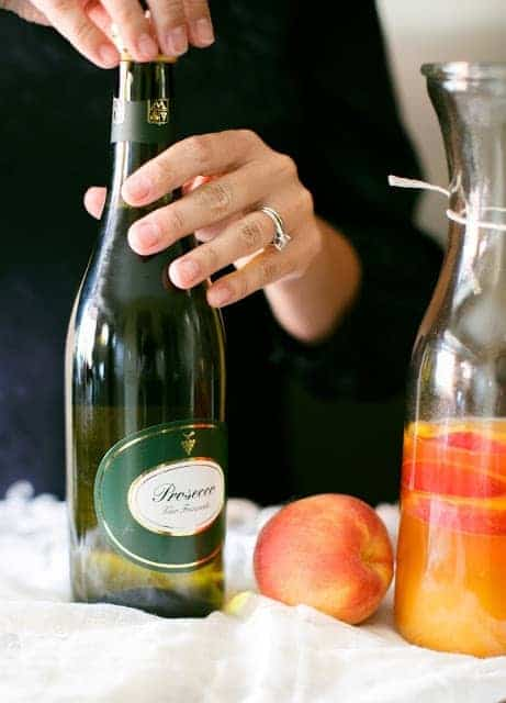 a glass carafe full of a prosecco sangria recipe, woman opening prosecco to the side.