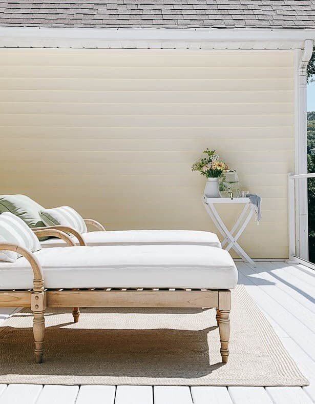 Two wooden lounge chairs placed on white vinyl decking at a lake house.