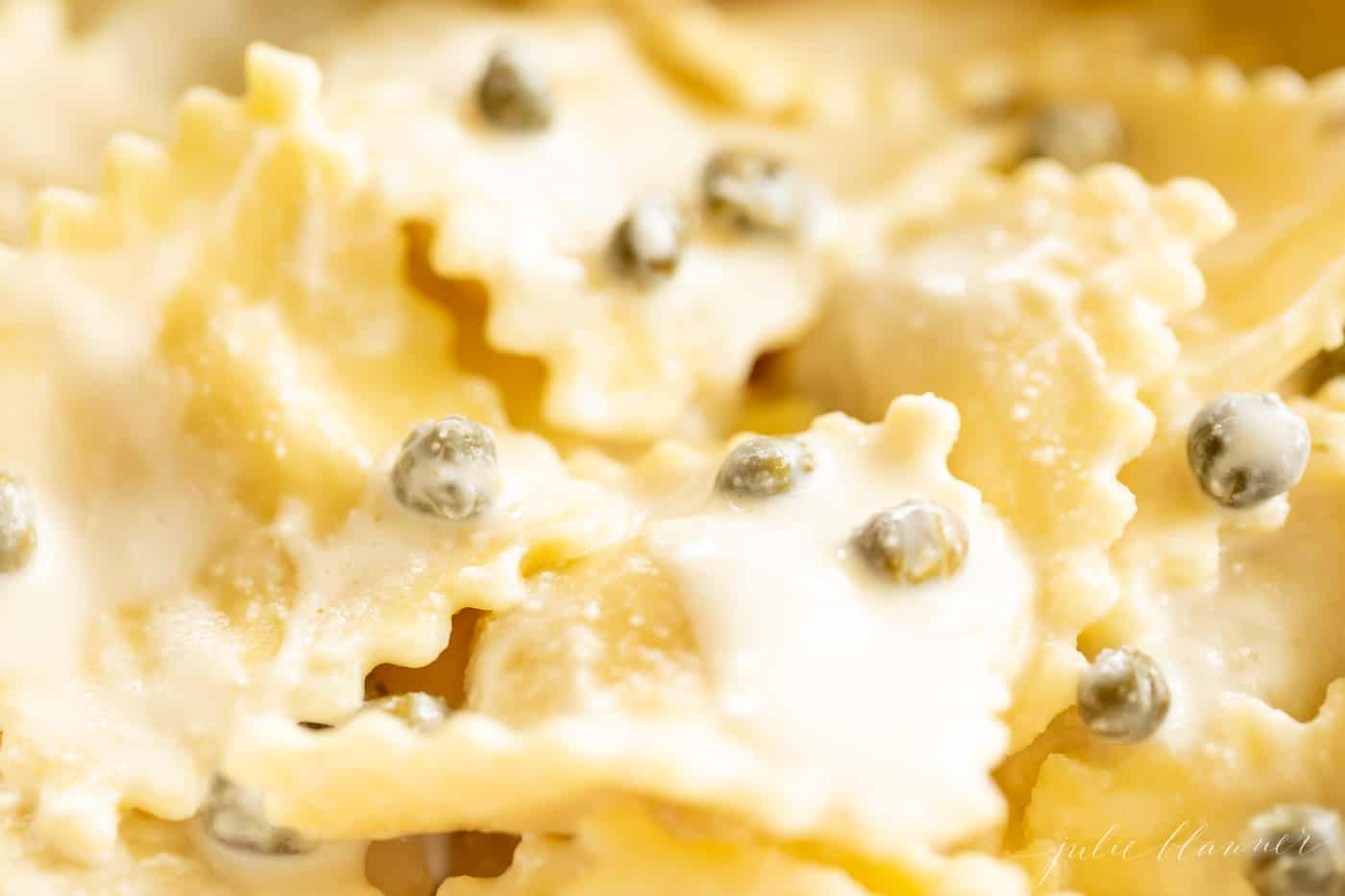 Close up of ravioli in a white wine lemon caper sauce