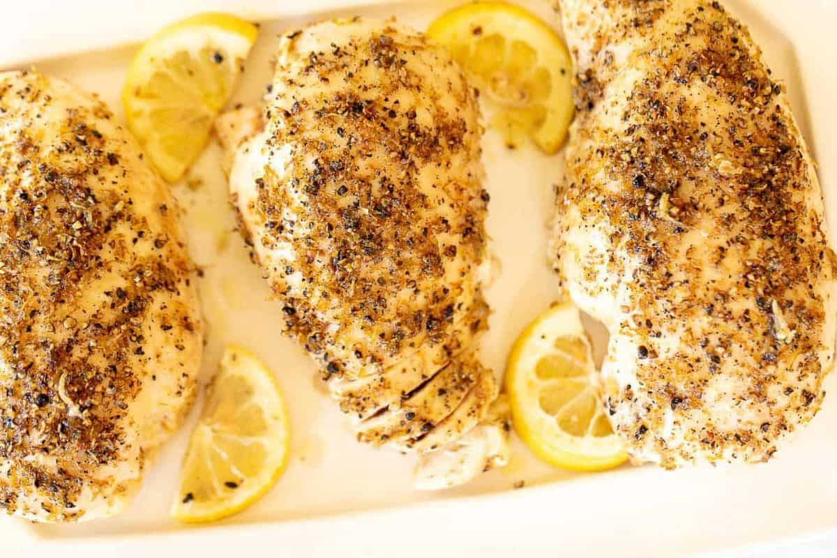 A white dish filled with lemon pepper chicken breasts, slices of lemon alongside.