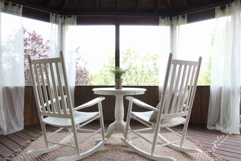 two rocking chairs on a screened in porch