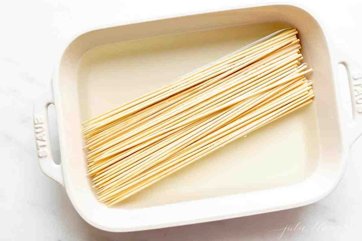 A white dish filled with water and bamboo skewers for grilling kabobs.
