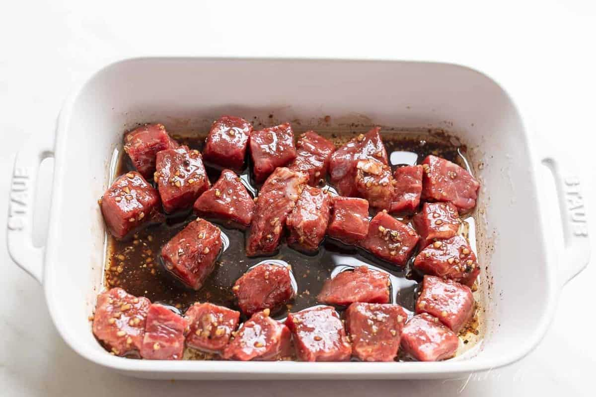 Sirloin steak in a steak kabob marinade in a white dish.