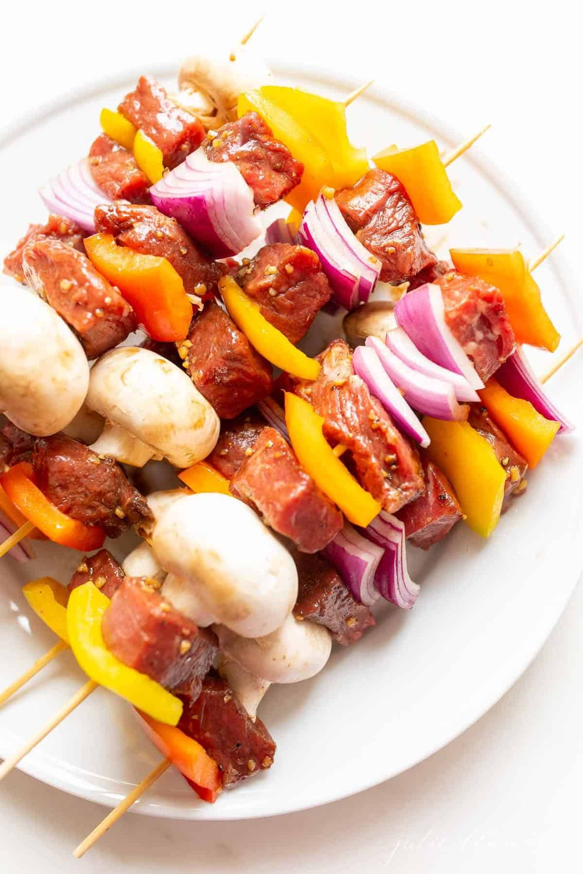 A platter full of skewers with veggies and raw steak for kabobs.