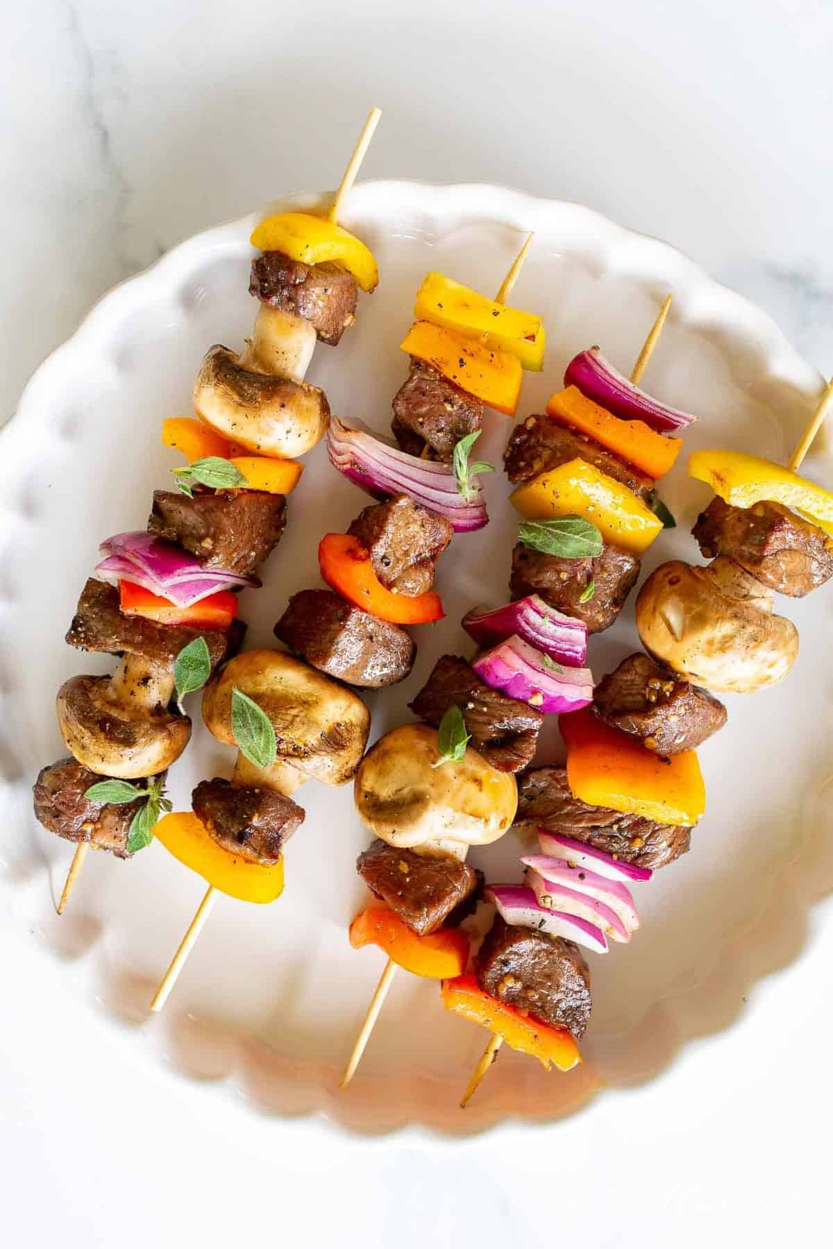 Grilled steak kabobs on a white platter.