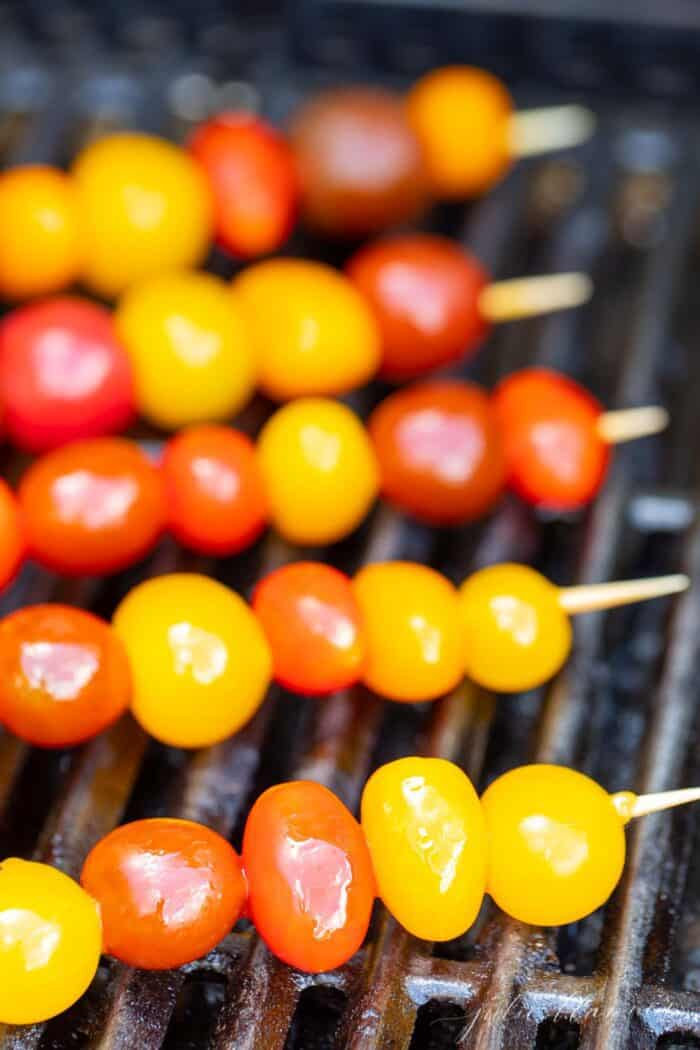 Cherry tomato skewers on a grill.