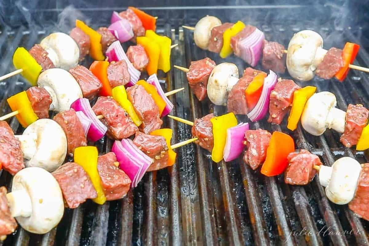 Wooden skewers with veggies and steak kabobs on the grill.