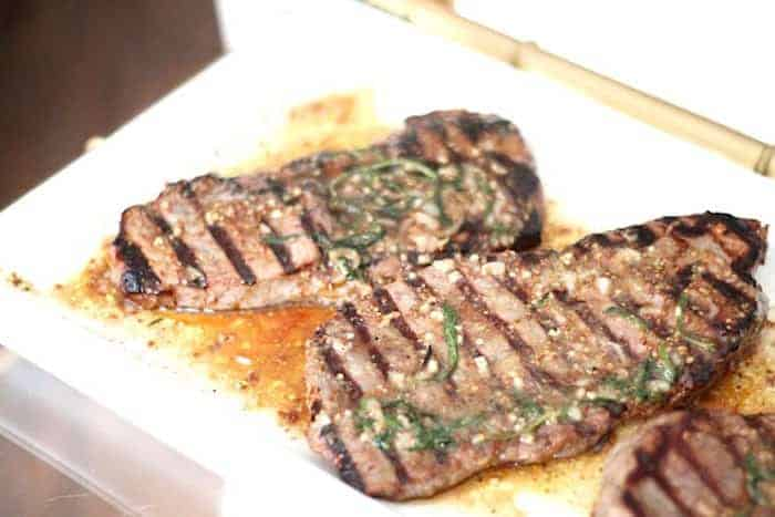 A white tray with grilled marinated steak.