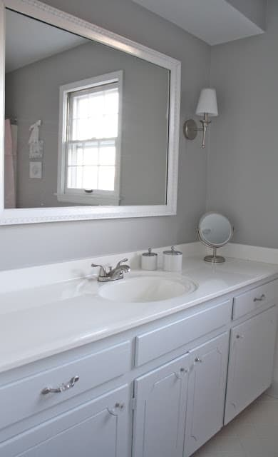 Bathroom with a white cabinet and gray walls.