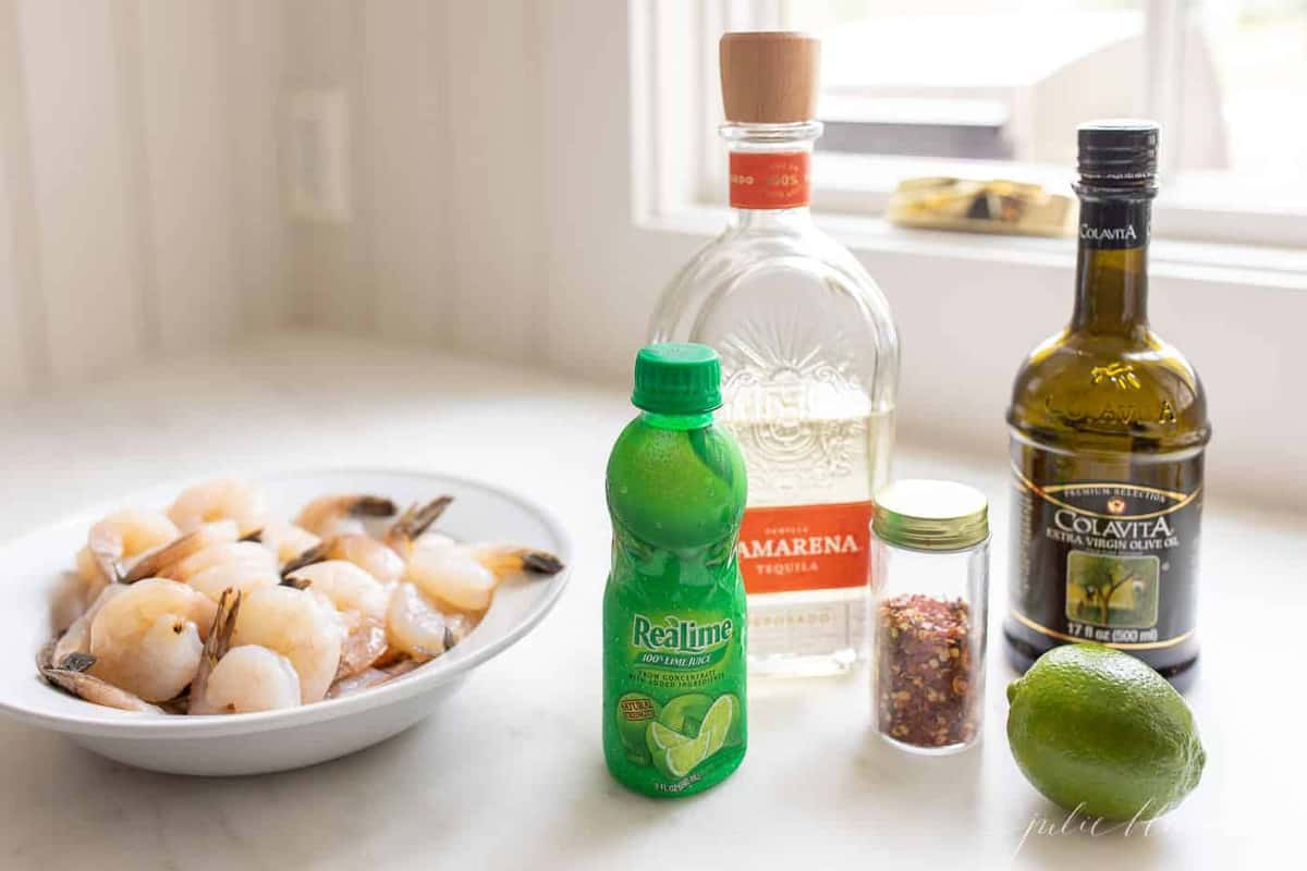 Ingredients for a tequila lime shrimp marinade with a platter of raw shrimp to the side.