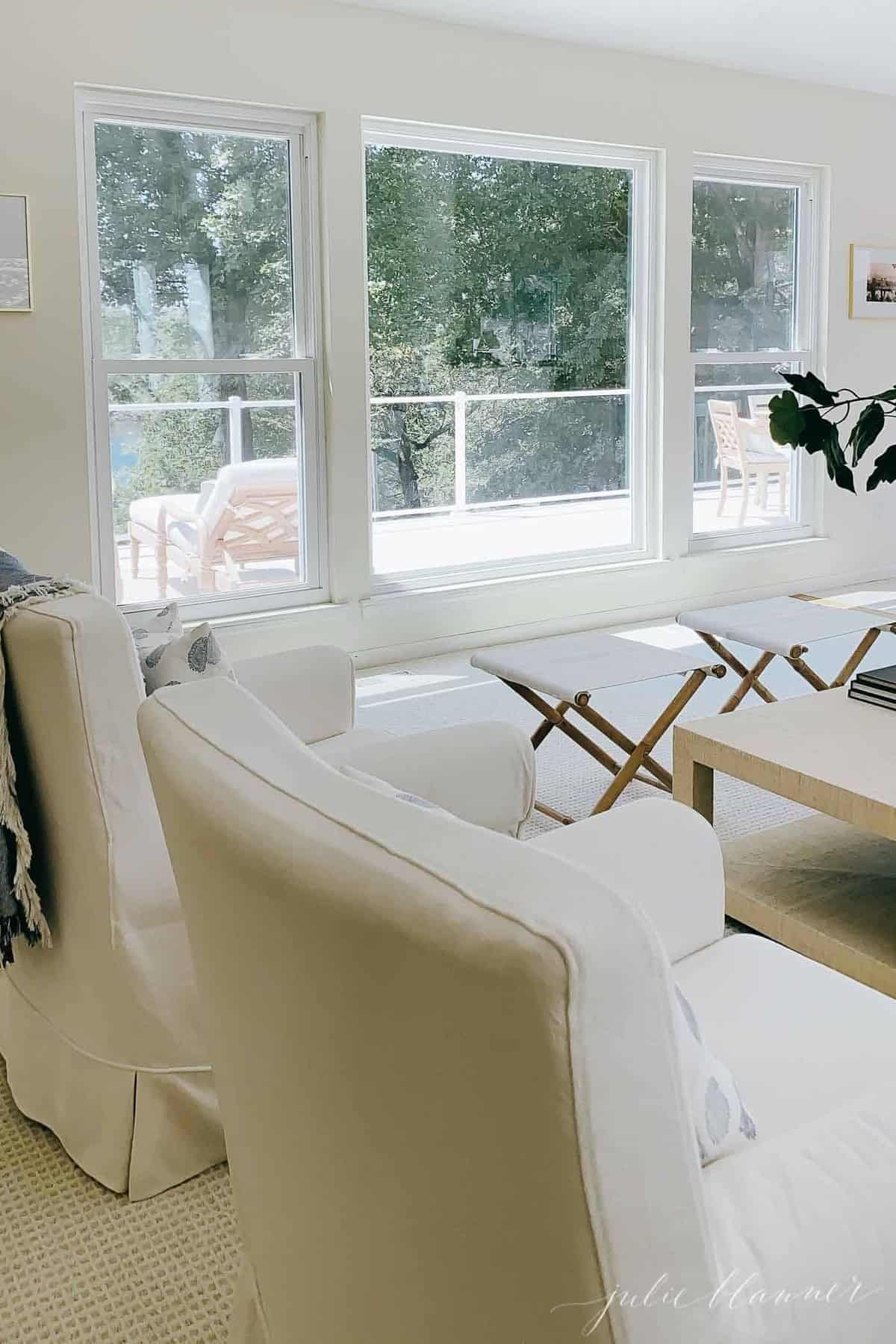 View of a white vinyl deck through large living room windows.