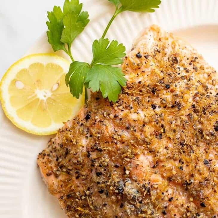 A white oval platter featuring a fillet of lemon pepper salmon, sliced lemons on the side.