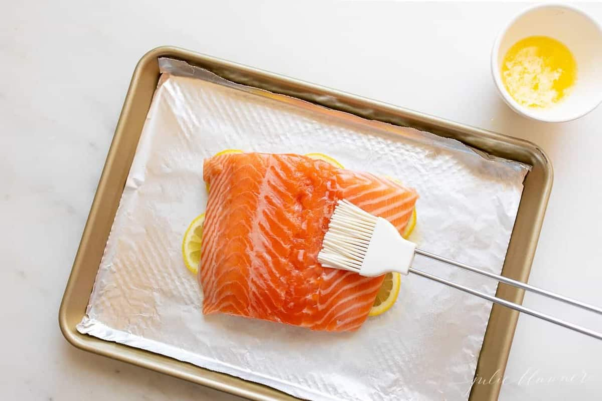 A single fillet of lemon pepper salmon on a foil lined aluminum sheet.