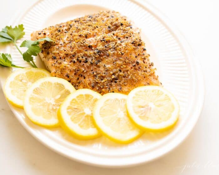 A white oval platter featuring a fillet of lemon pepper salmon, sliced lemons on the side.