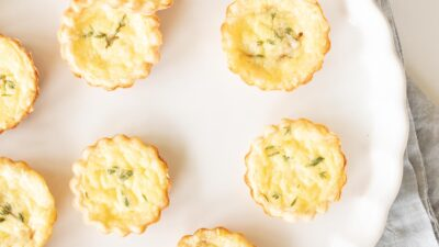 A white scalloped dish filled with small cheddar cheese tarts.