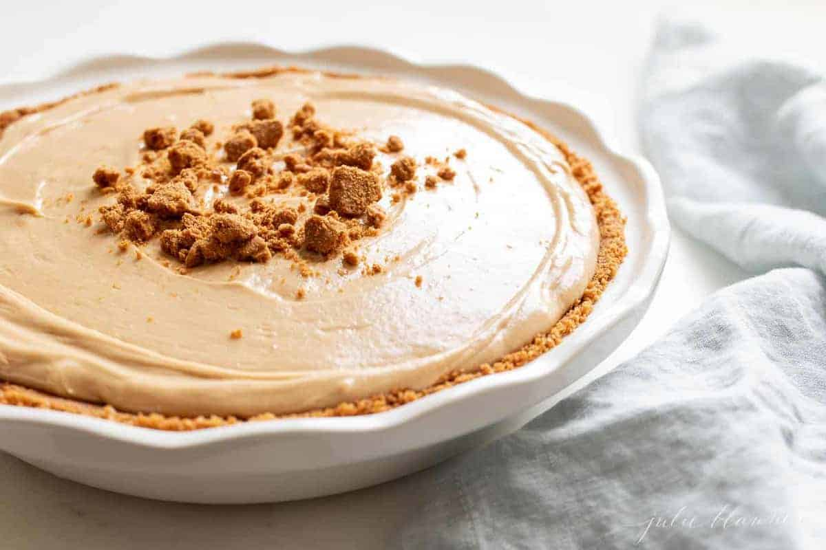 A white pie plate filled with a cookie butter cheesecake recipe.