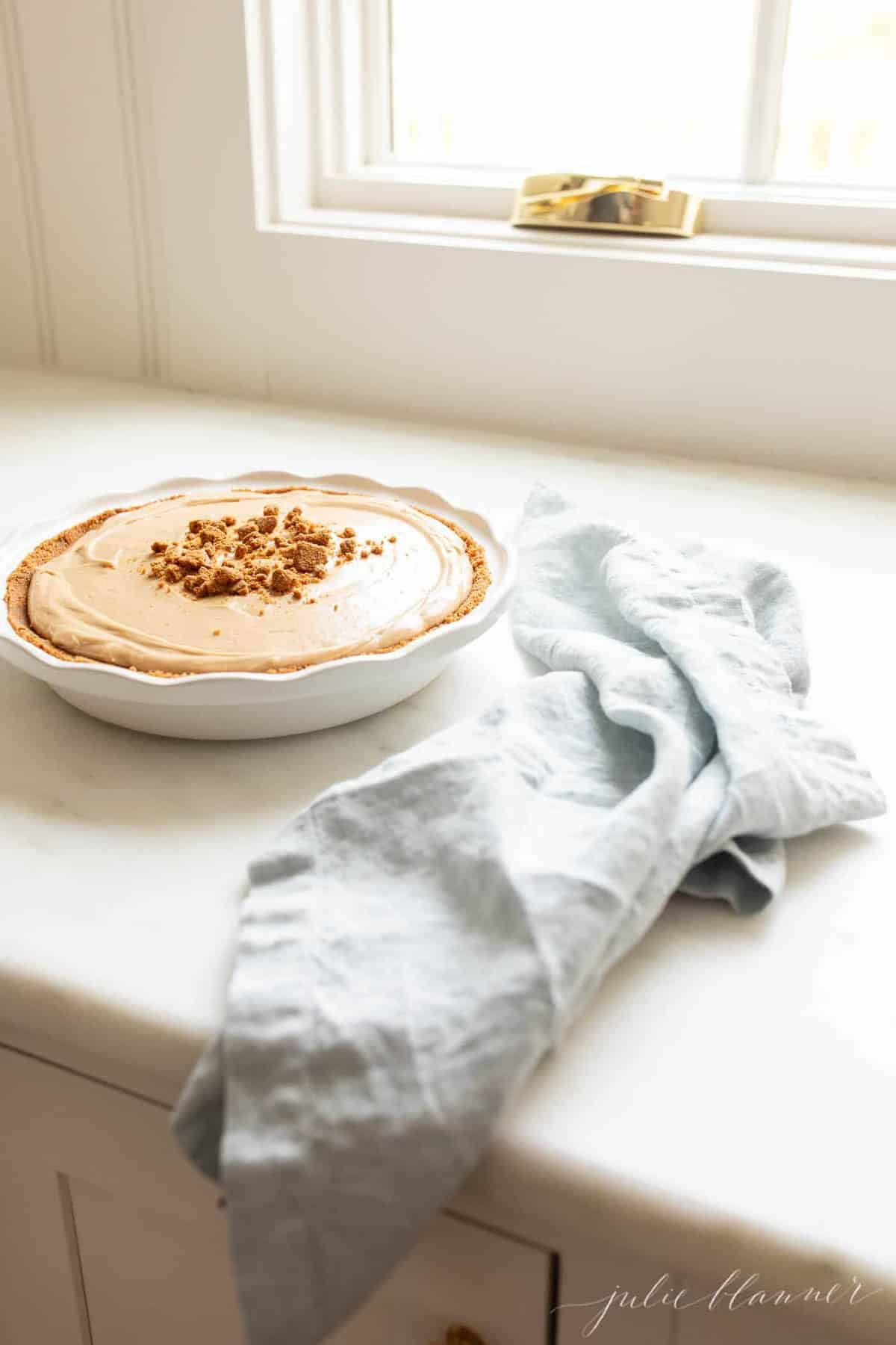 A white pie plate filled with a cookie butter cheesecake recipe, blue napkin to the side and kitchen window in backgorund.