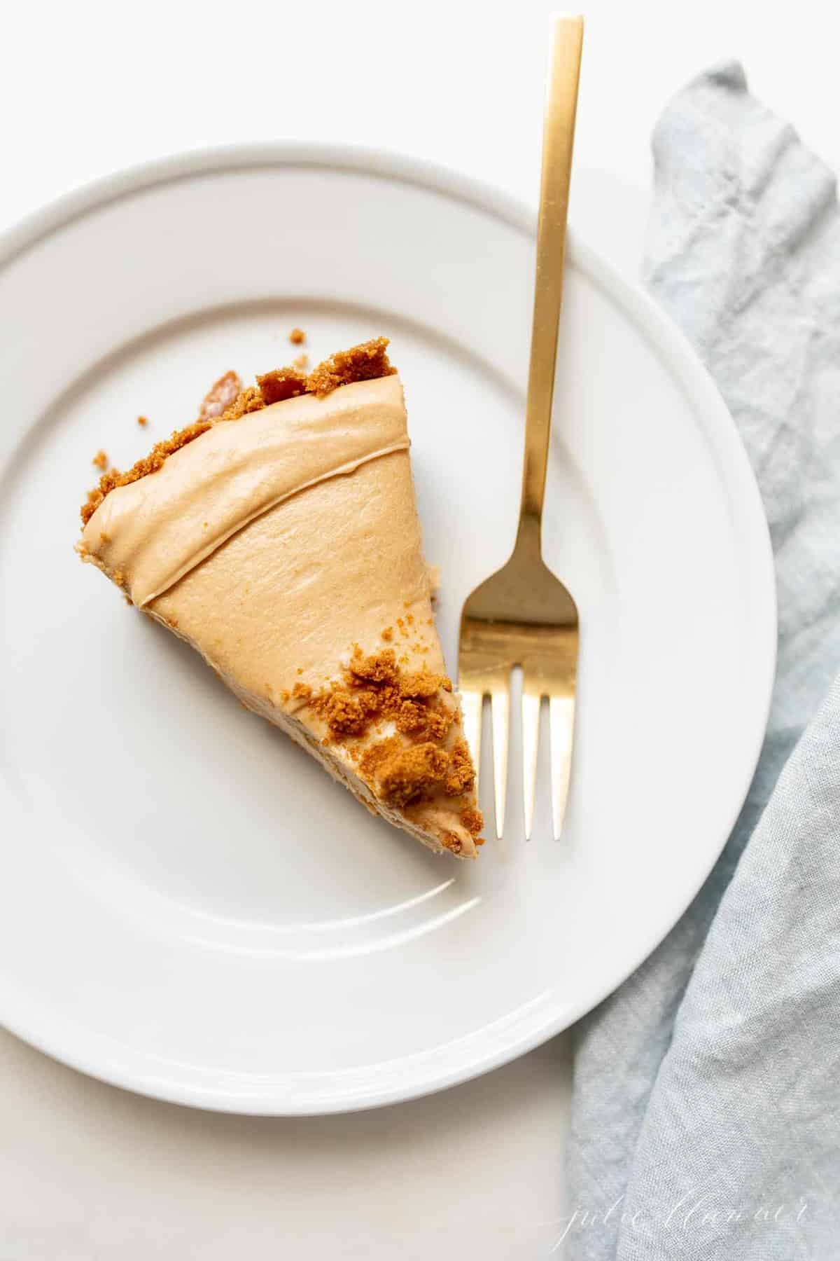 A white plate with gold fork to the side of a slice of cookie butter cheesecake.