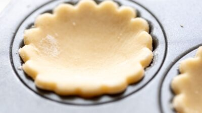 A scalloped cream cheese pie crust cut out, resting in a muffin tin.