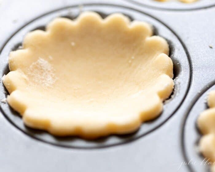 A scalloped cream cheese pie crust cut out, resting in a muffin tin.