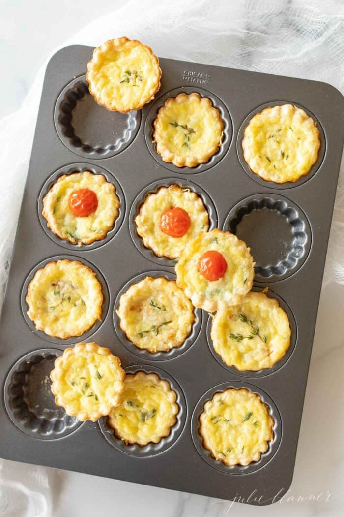 A metal tart pan with small cheese tarts with a cream cheese pie crust recipe as the scalloped edges.
