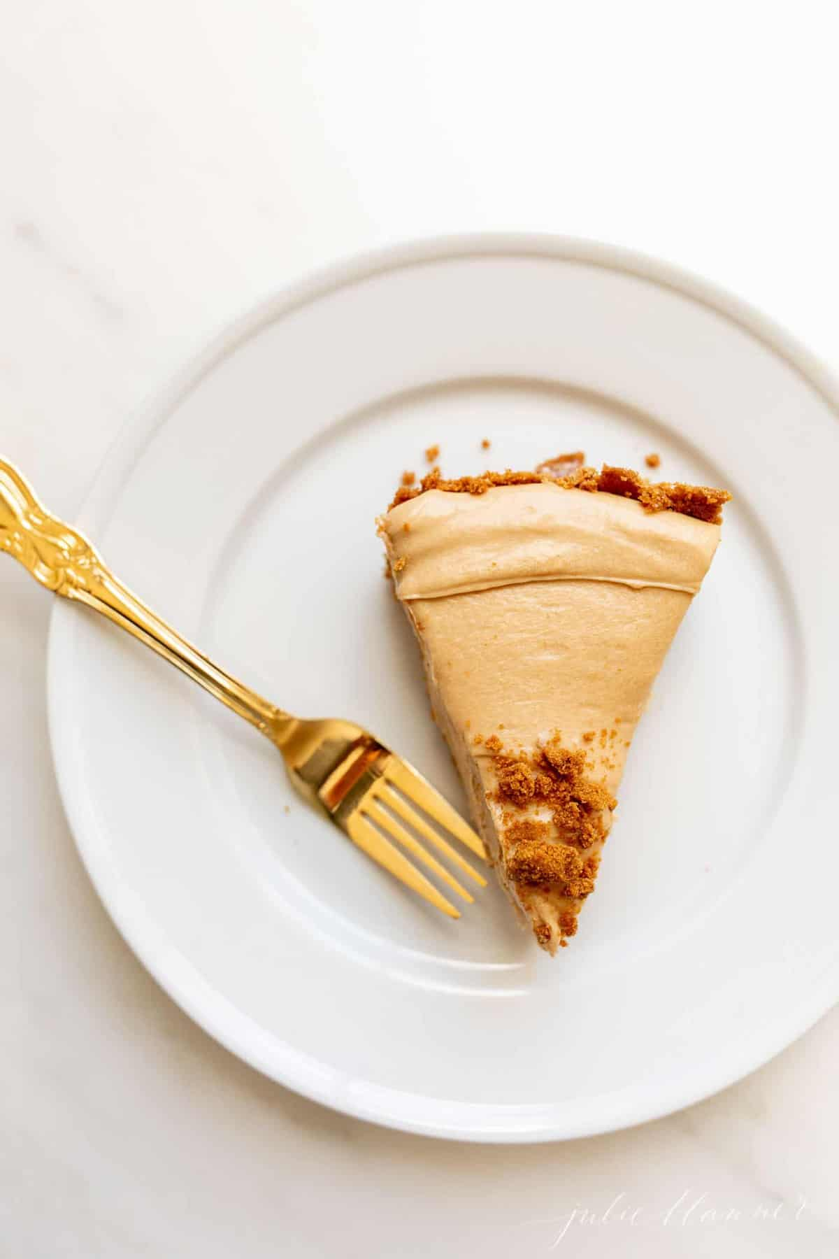 A white plate with gold fork to the side of a slice of no bake cookie butter cheesecake.