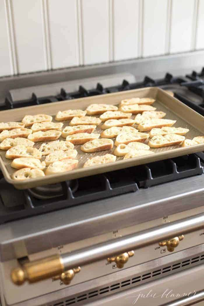 Crostini slices on a sheet pan on top of a stovetop.