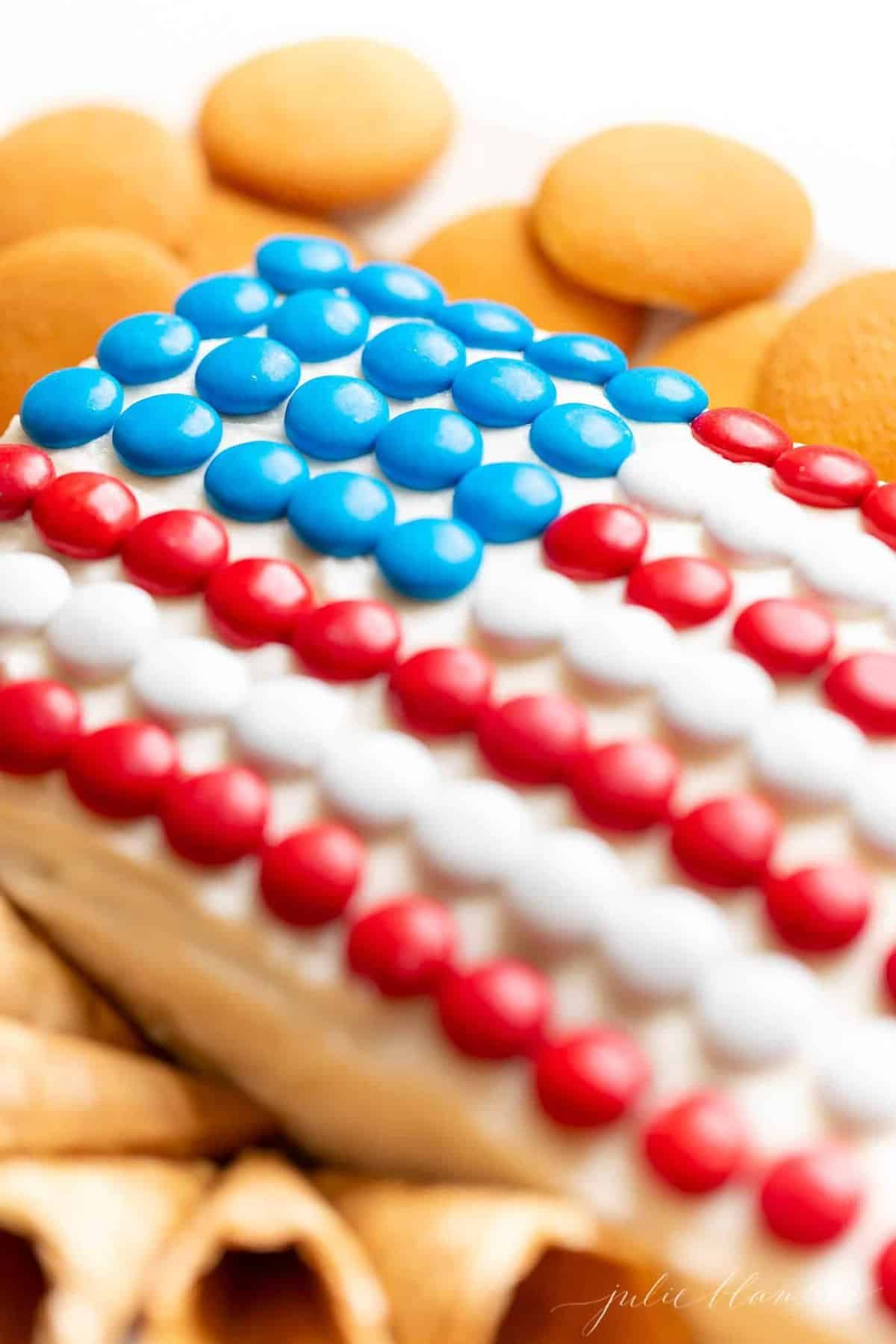 A frosted fourth of july flag dessert, covered in m&ms, crackers surrounding.