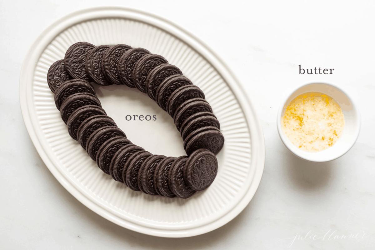 Prato branco cheio de oreos e um ramekin branco cheio de manteiga derretida como ingredientes para fazer uma receita de crosta de biscoito oreo.