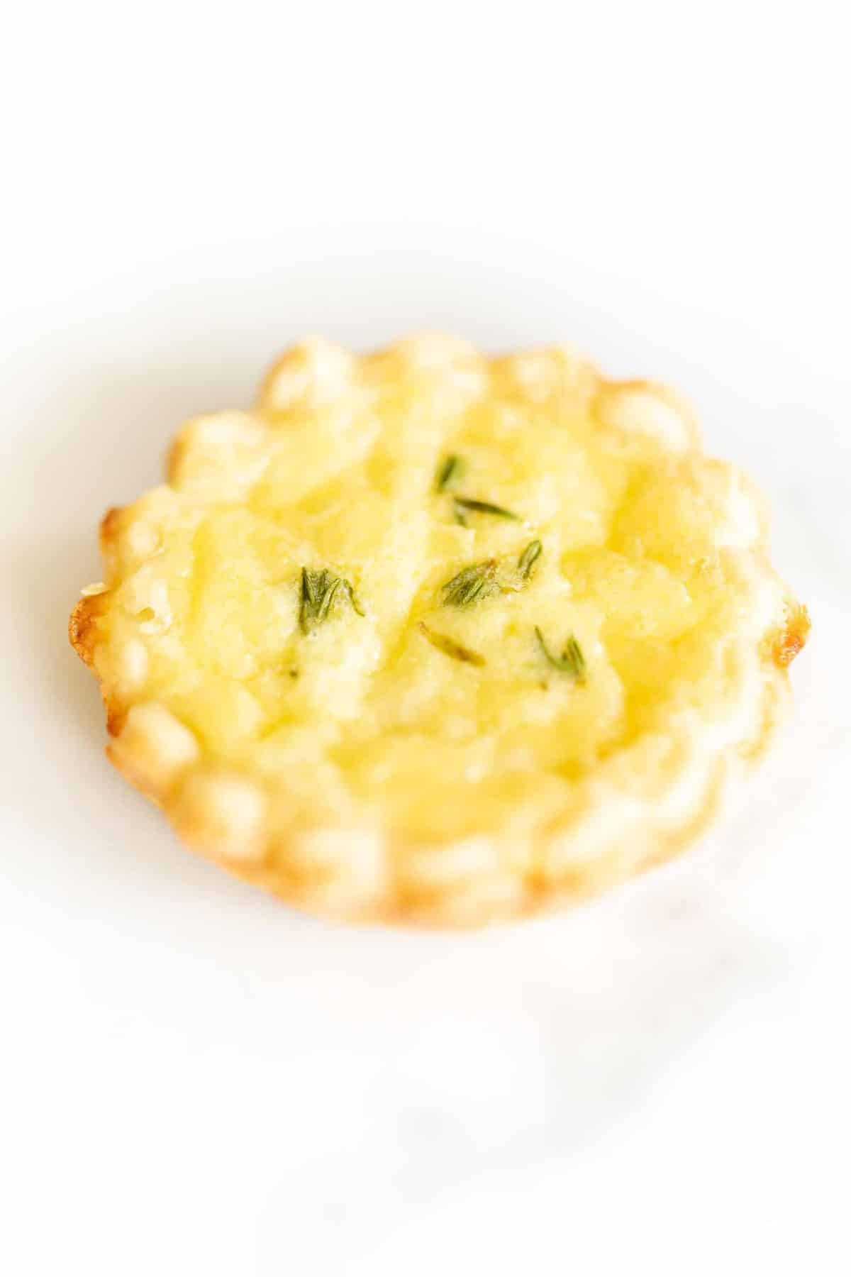 A small cheese tart with a cream cheese pie crust on a marble surface.