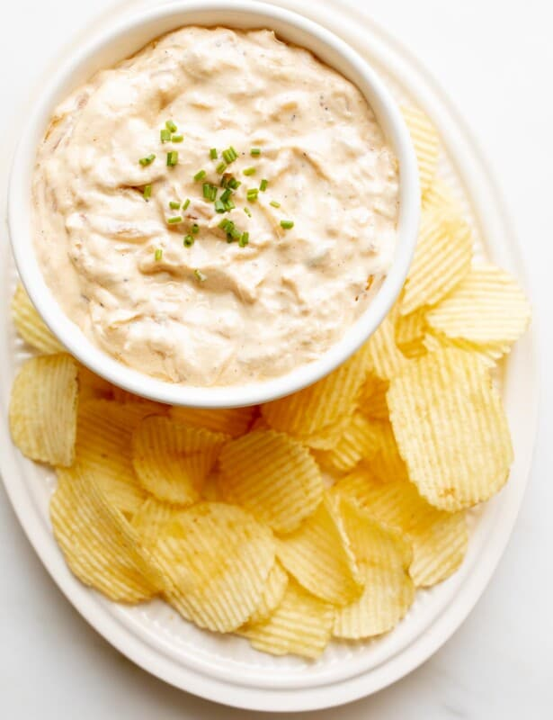 french onion dip in bowl on platter with ruffle chips