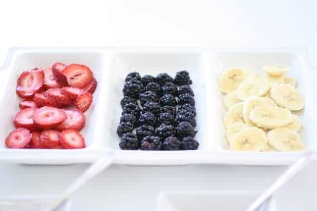 A white partitioned tray full of fruit for mini fruit pizza cookies.