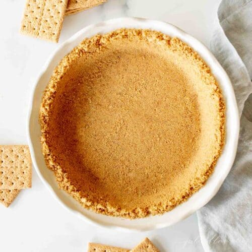 graham cracker pie crust in white pie dish with graham crackers surrounding it