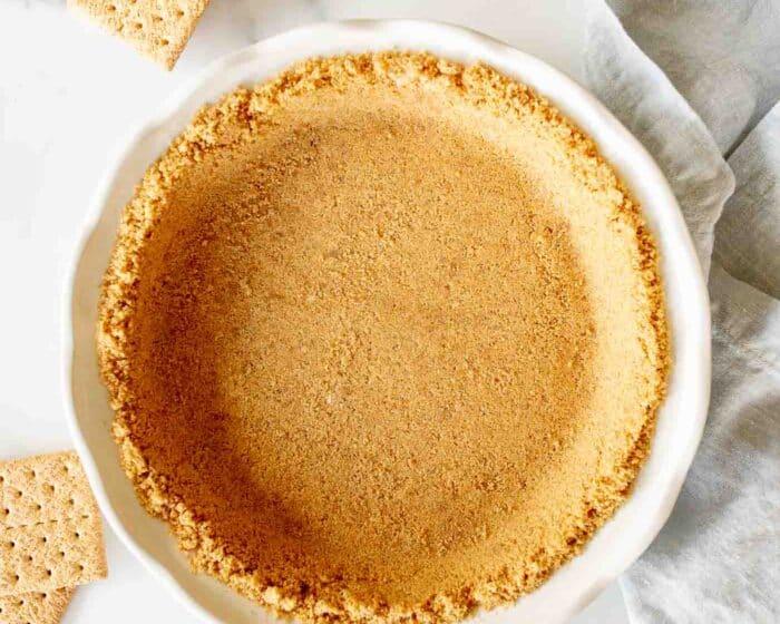 graham cracker crust in white pie dish with crackers surrounding it